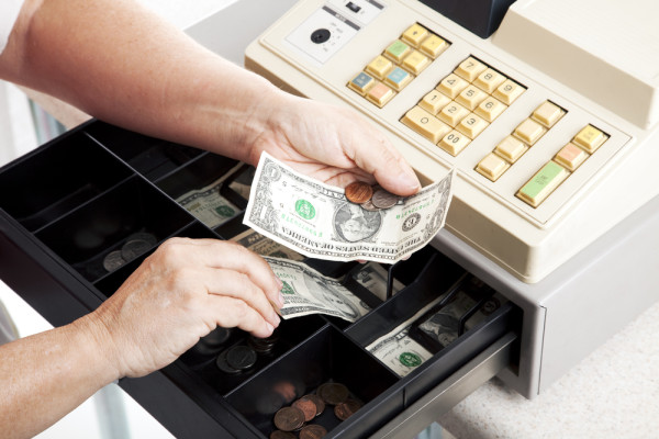 Horizontal view of an open cash register drawer asa a cashier makes change.